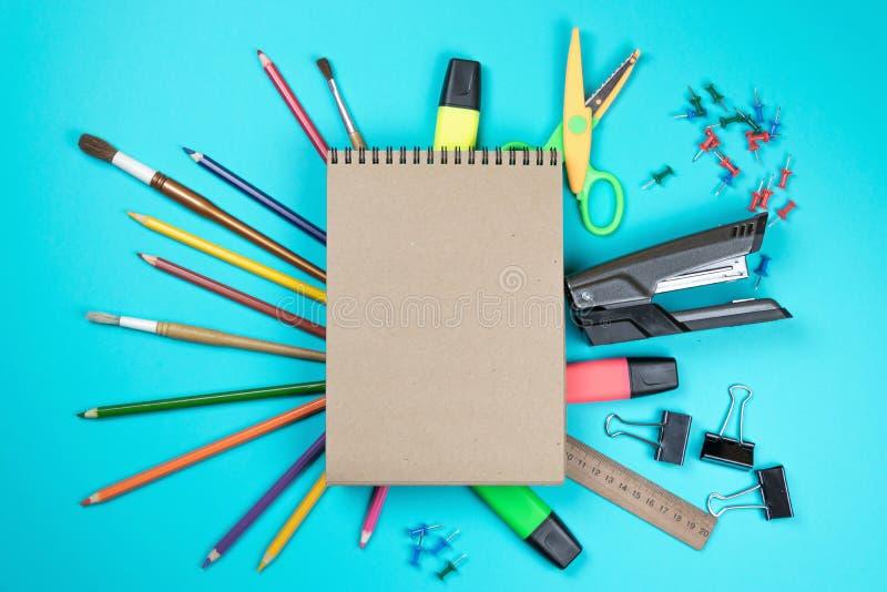 Kantoorbehoeften kleurrijke die het schrijven de pennenpotloden van hulpmiddelentoebehoren, Kraftpapier-document op blauwe achter stock foto's