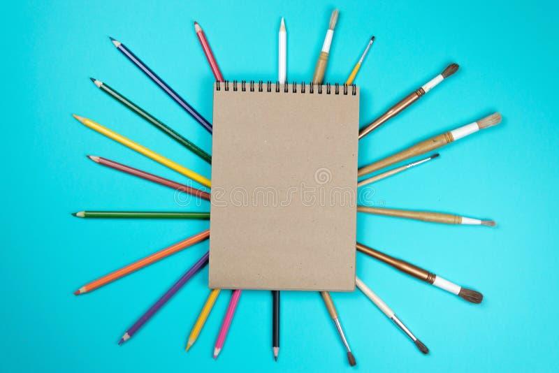 Kantoorbehoeften kleurrijke het schrijven de pennenpotloden van hulpmiddelentoebehoren, Kraftpapier-document dat op blauwe achter stock afbeeldingen