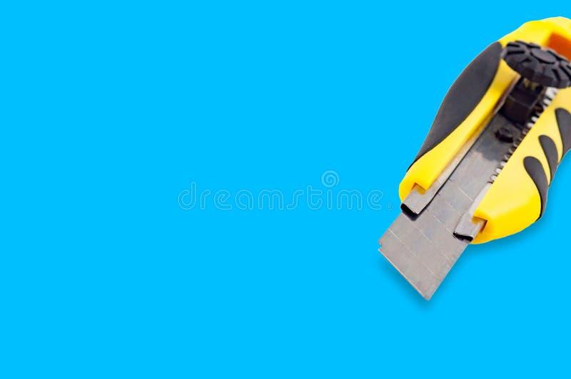 Kantoorbehoeftenmes met geel en zwart plastic handvat op blauwe achtergrond stock afbeelding