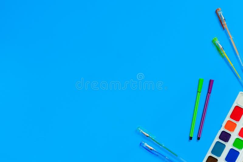 kantoorbehoeftentoebehoren - pennen, tellers, verven op blauwe achtergrond Samenstellingsprototype, terug naar schoolconcept met  stock foto