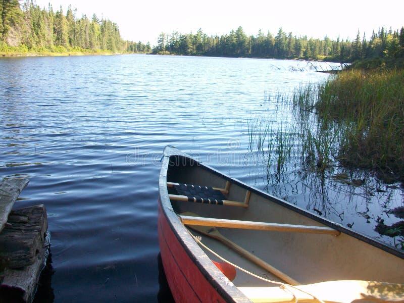 Kanu angekoppelt durch ruhigen See stockfotos