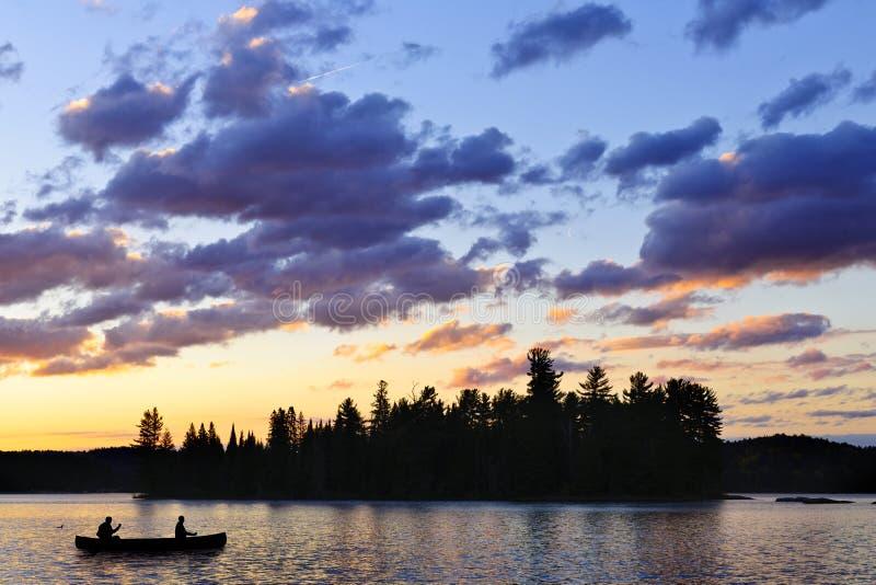 Kanu auf See bei Sonnenuntergang lizenzfreie stockbilder