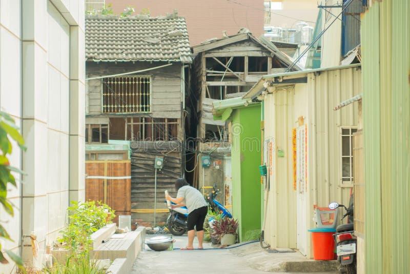 Kaohsiung/Taiwan-18 05 2018: Biedny okręg w Kaohsiung mieście Kobieta myje ich zakończenia na ulicie zdjęcie royalty free