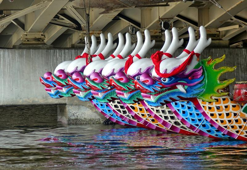 A Row of Traditional Dragon Boats. KAOHSIUNG, TAIWAN -- JUNE 10, 2018: A row of dragon boats with the traditional figureheads is being prepared for the upcoming royalty free stock images