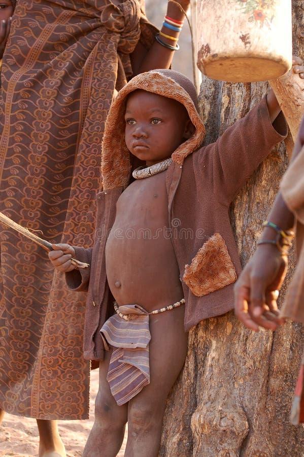 KAOKOVELD, NAMIBIA - OKT 13, 2016: Ragazzo non identificato di Himba in un piccolo villaggio Il bambino sta aiutando proteggendo  fotografia stock