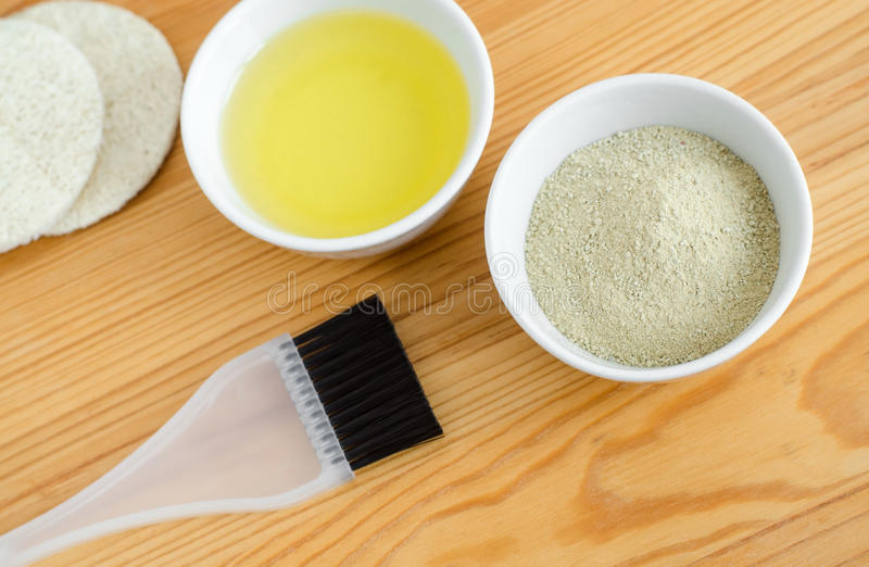 Kaolinlehmpulver und Olivenöl in kleine keramische Schüsseln Bestandteile von selbst gemachten Kosmetik stockfotografie