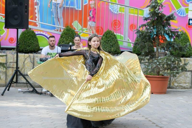 Kapacitet av en ung dansare Liten flickadansen poserar Anförande av en ung flicka i en svart klänning Svänga en gul fan arkivbild