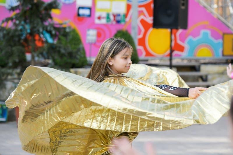 Kapacitet av en ung dansare Liten flickadansen poserar Anförande av en ung flicka i en svart klänning Svänga en gul fan arkivfoton