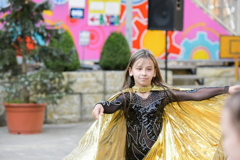 Kapacitet av en ung dansare Liten flickadansen poserar Anförande av en ung flicka i en svart klänning Svänga en gul fan arkivbilder