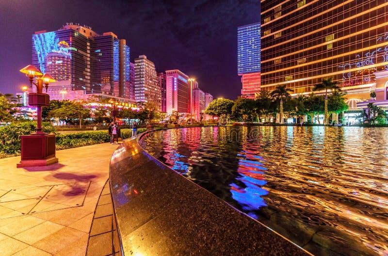 Kapacitet sjö vid ingången av Macao Wynn Palace på natten med arkitektonisk och gatabelysning Scenisk Macao cityscape arkivbilder