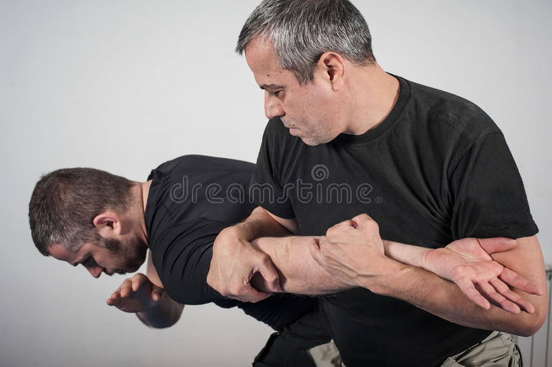 Kapap instructor demonstrates arm bar techniques. With his student royalty free stock photos