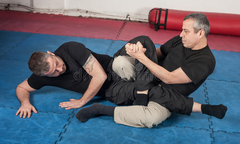 Kapap instructor demonstrates ground fighting techniques. With his student royalty free stock photos