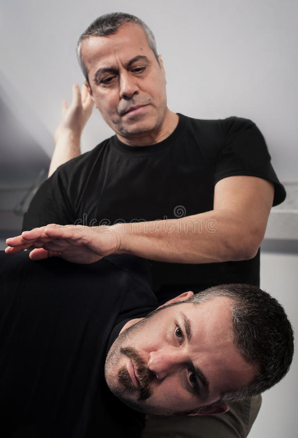 Kapap instructor demonstrates standing arm lock techniques. With his student stock photo