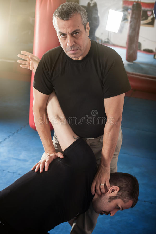 Kapap instructor demonstrates standing arm lock techniques. With his student stock image