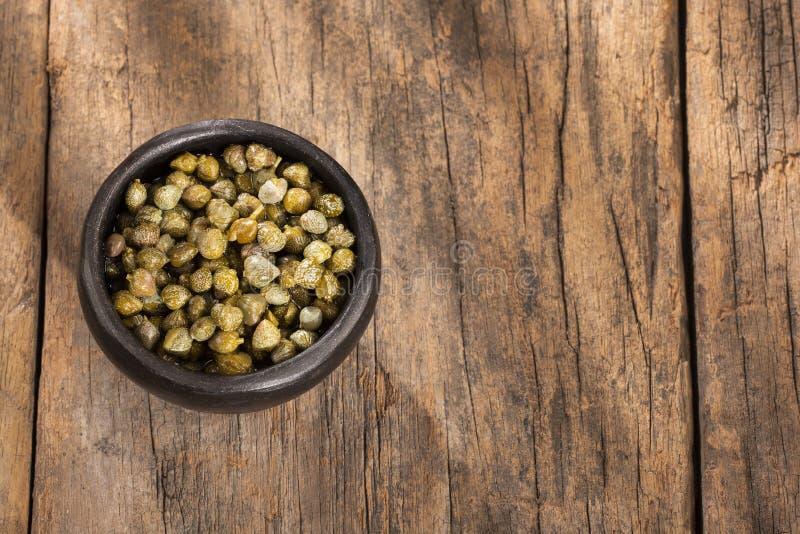 Kapary w drewnianym pucharze - Capparis spinosa Drewniany tło obraz stock