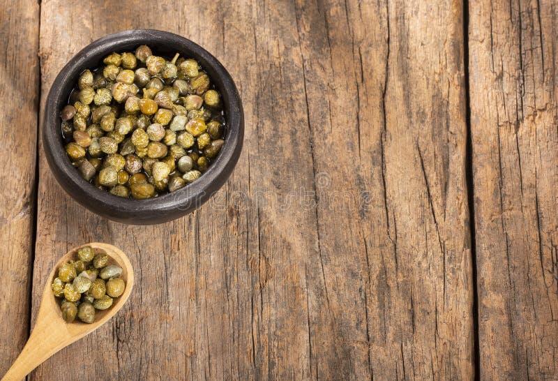 Kapary w drewnianym pucharze - Capparis spinosa Drewniany tło fotografia stock