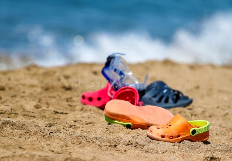 Kapcie - kroks i maska na piasek plaży blisko wody morskiej - symbol lato fotografia royalty free
