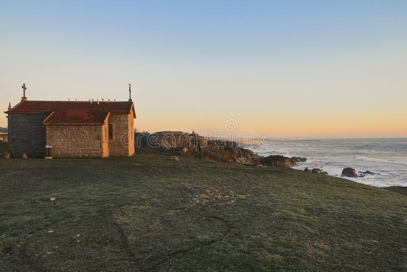 Kapel die de oceaan overzien bij zonsondergang stock afbeelding