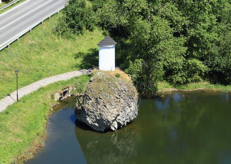 Kapel op rots in vijver stock foto