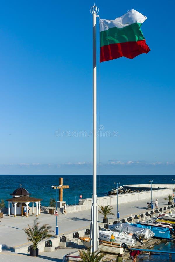 Kapel van Sinterklaas in de zeehaven van de stad van de kusttoevlucht van Pomorie en de nationale vlag van Bulgarije in de voorgr stock afbeeldingen
