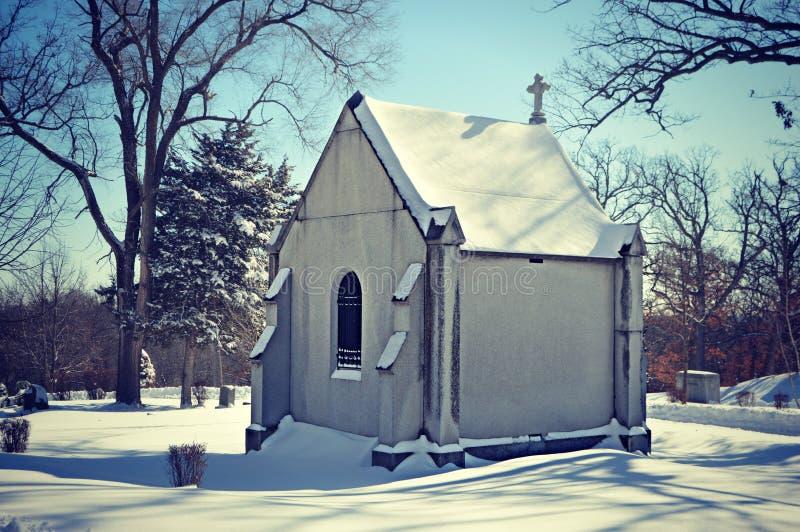 Kapell i snöig kyrkogård royaltyfri bild