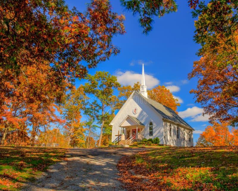 Kapelle auf einem Hügel mit Fallfarben und einem blauen Himmel stockfoto