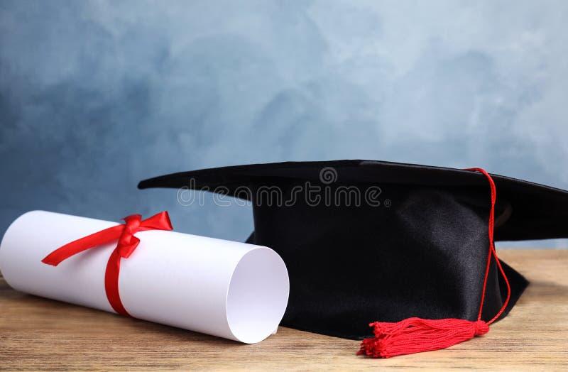 Kapelusz i dyplom studenta na stole przy jasnoniebieskim tle obrazy stock