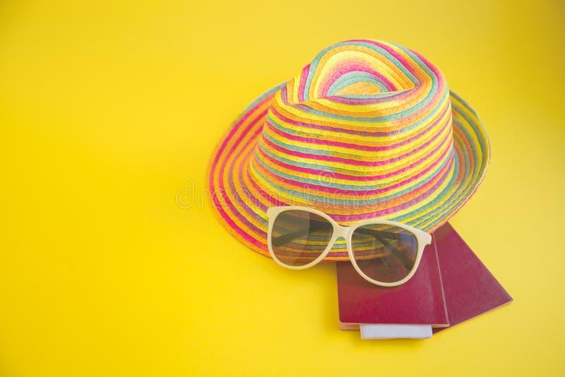Kapelusz, okulary przeciwsłoneczni, paszport na żółtym tło Odgórnego widoku esse zdjęcia royalty free
