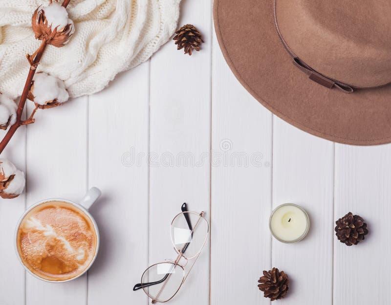 Kapelusz, pulower, kawa i inne rzeczy na białym drewnianym tle, zdjęcia stock