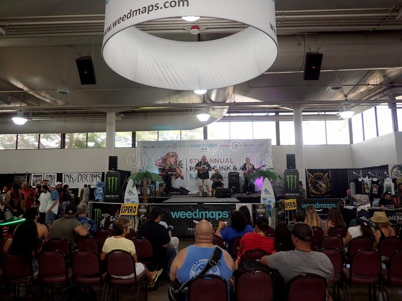 Kapena Band Jams on Weedmaps stage as crowd sits. Honolulu -  August 6, 2017: Kapena Band Jams on Weedmaps stage as crowd sits and listens at the Hawaii Tattoo stock photo
