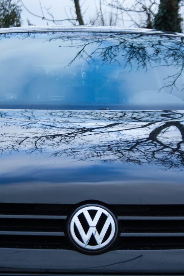 Kapiszon czarny samochód z srebnym wolkswagena emblematem Kapiszon odbija drzewa i nieba obraz royalty free