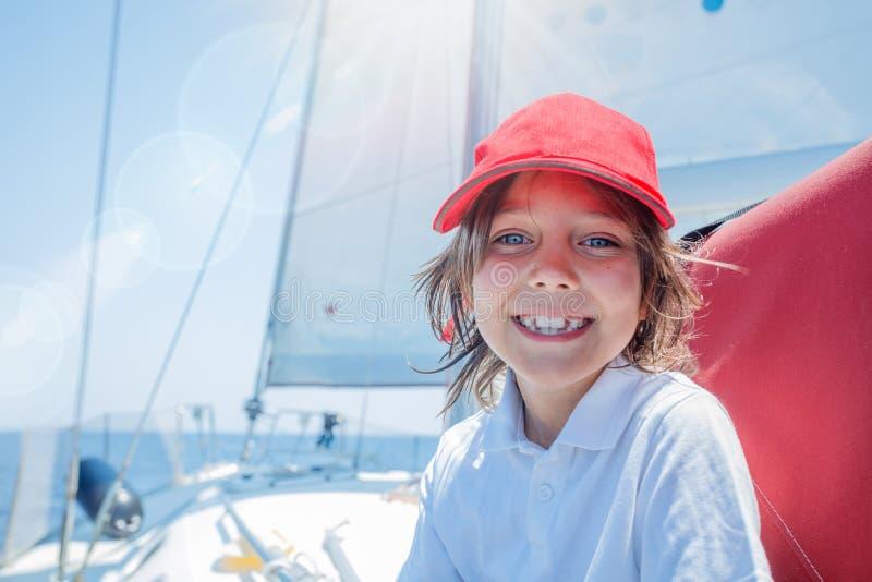 Kapitän des kleinen Jungen an Bord von Segeljacht auf Sommerkreuzfahrt Reiseabenteuer, Segelsport mit Kind auf Familienurlaub stockfotografie
