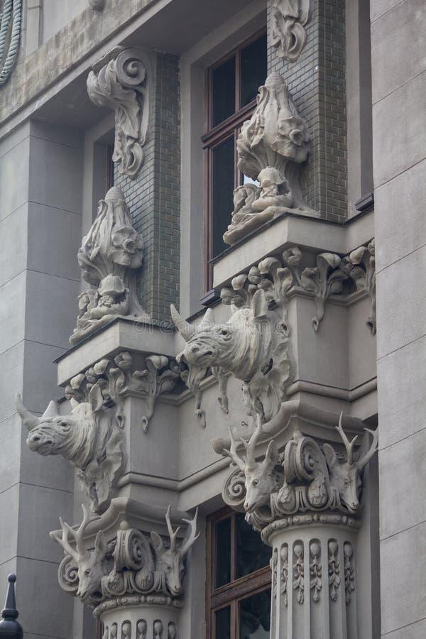 Kapitaal en het bovenste gedeelte van de voorgevel met beeldhouwwerken van dieren op het historische Art Nouveau-gebouw royalty-vrije stock foto