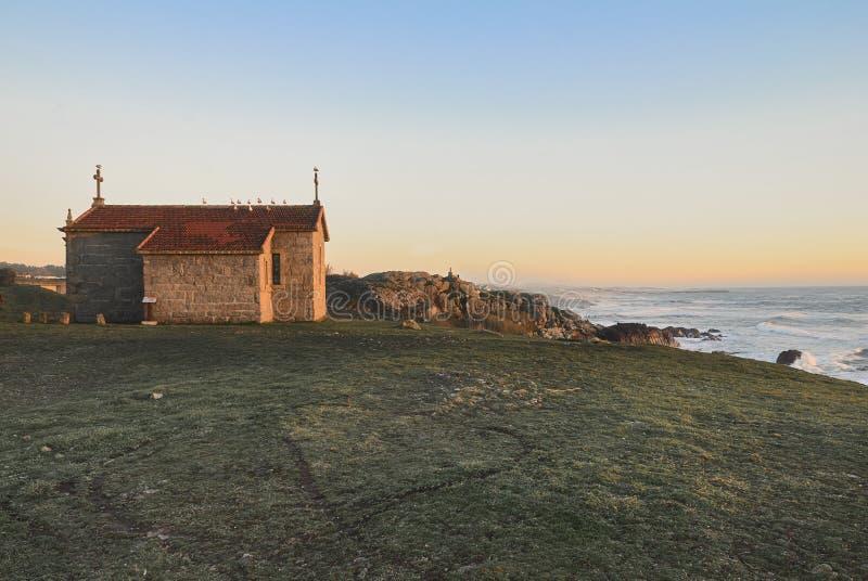 Kaplica przegapia ocean przy zmierzchem obraz royalty free