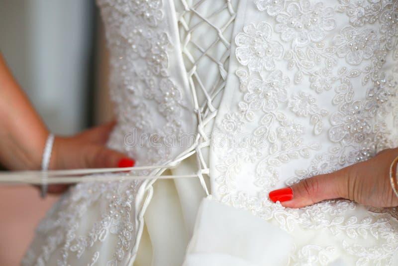 Kappa för bruddressingbröllop, brudtärna som hjälper upp den pålagda bröllopsklänningen på bruden, lyxigt brud- klänningslut arkivfoto