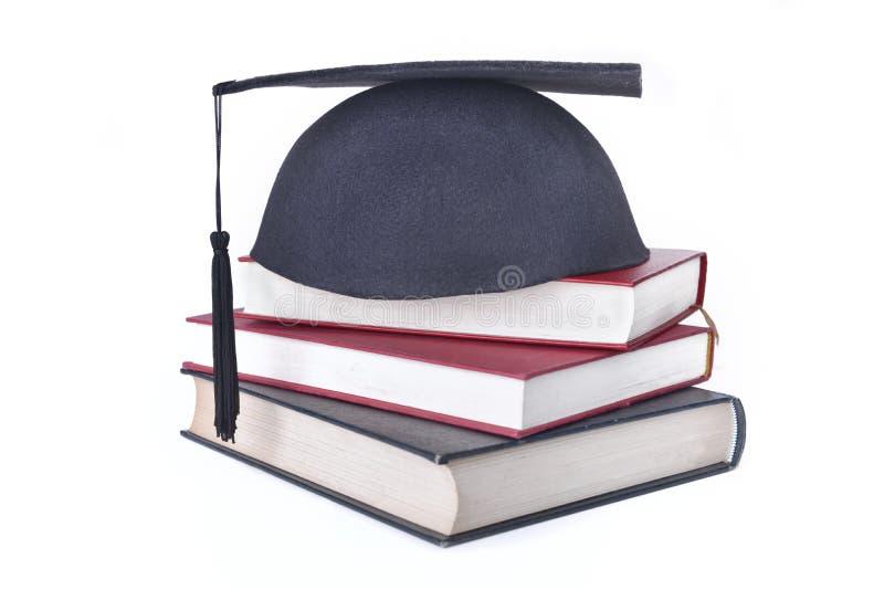 Kappe setzte die Bücher gestapelt lokalisiert auf weißen Hintergrund stockfotografie