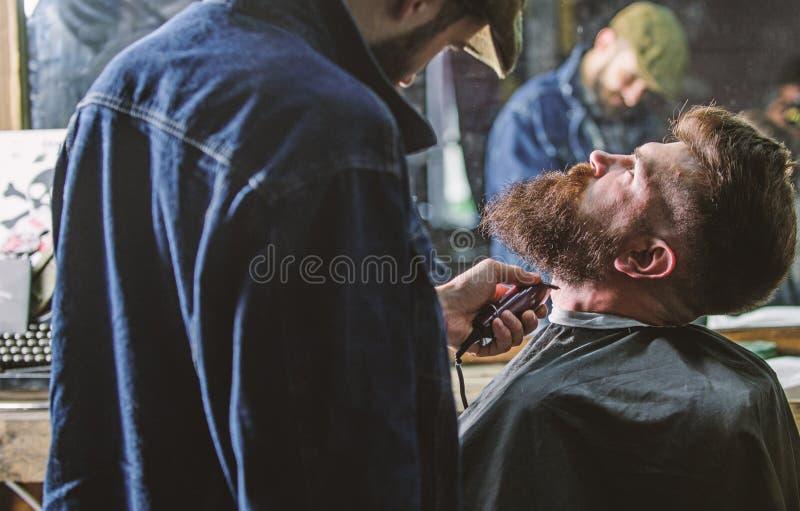 Kapper bezig met het verzorgen baard van hipstercli?nt, spiegelbezinning op achtergrond Hipster met baard met kaap wordt behandel stock fotografie