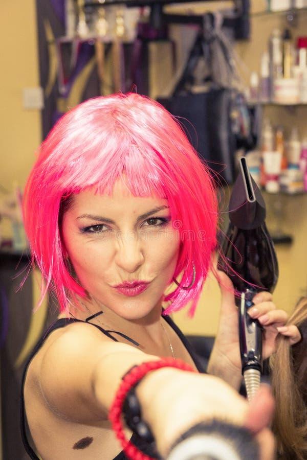 Kapper bij de salon met roze pruik op haar het hoofd glimlachen en p royalty-vrije stock fotografie