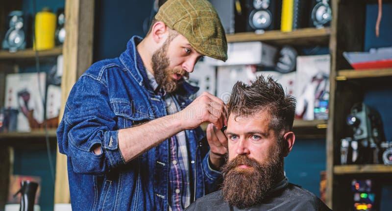 Kapper in denimjasje bezig met het in orde maken hipster, herenkapperachtergrond Cliënt met baard en snor wordt behandeld die met stock foto