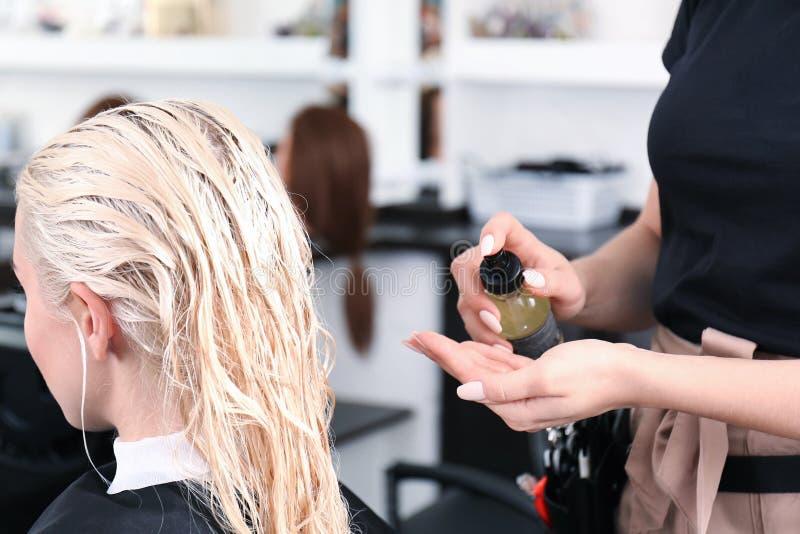 Kapper die balsem op blonde` s haar gebruiken stock afbeeldingen