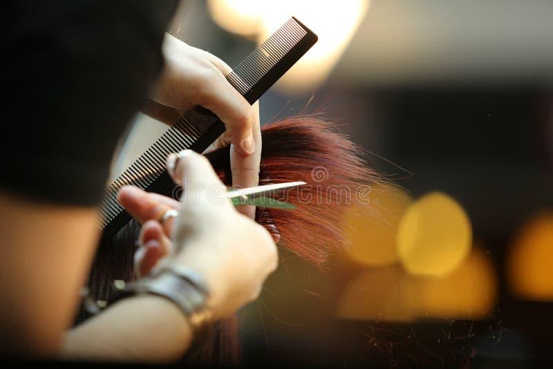 Kapper die bruin haar snijden stock afbeeldingen