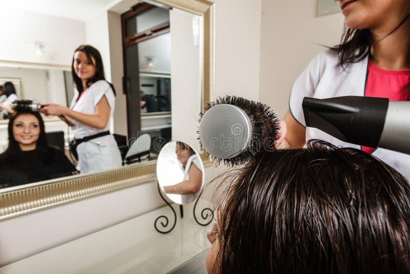 Kapper die donker vrouwelijk haar drogen die professionele hairdryer gebruiken stock fotografie