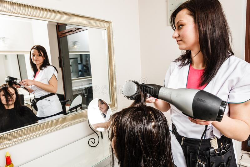 Kapper die donker vrouwelijk haar drogen die professionele hairdryer gebruiken royalty-vrije stock fotografie