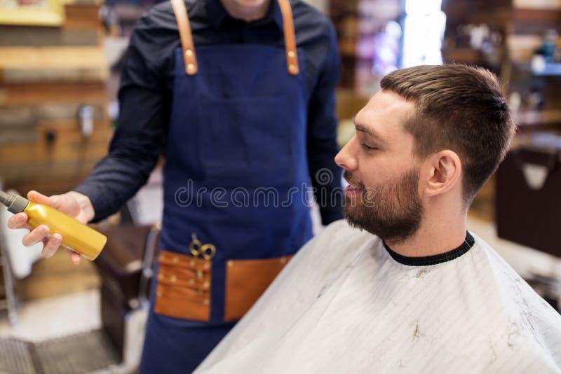 Kapper die haar het stileren nevel tonen aan mannelijke klant stock afbeelding