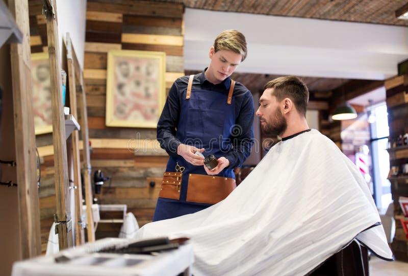 Kapper die haar het stileren was tonen aan mannelijke klant stock fotografie