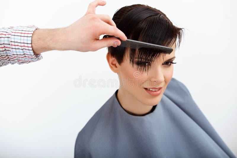 Kapper die Kapsel doen Brunette met Kort Haar in Salon royalty-vrije stock afbeelding