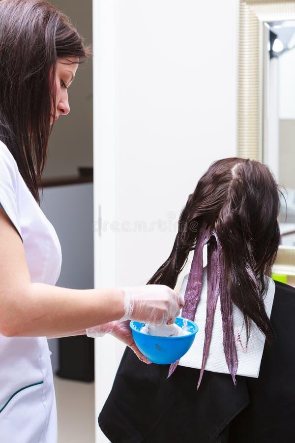 Kapper die kleuren vrouwelijke klant toepassen bij salon, die haarverf doen royalty-vrije stock fotografie