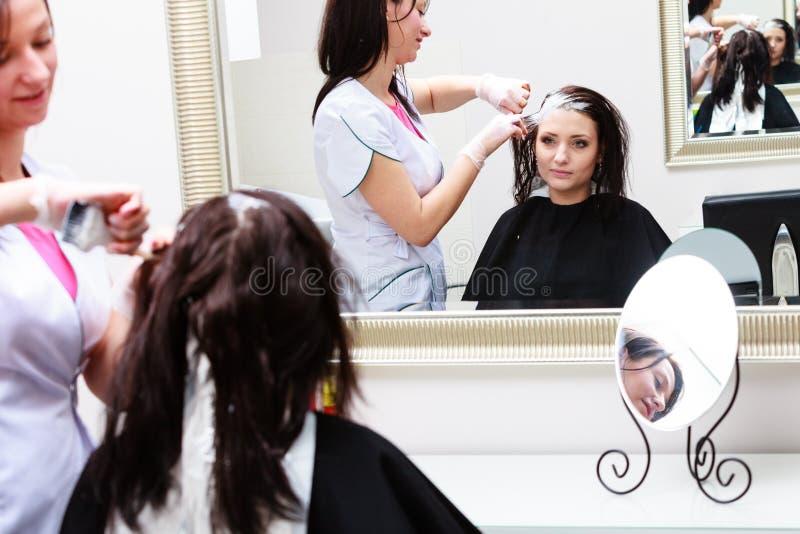 Kapper die kleuren vrouwelijke klant toepassen bij salon, die haarverf doen royalty-vrije stock afbeeldingen