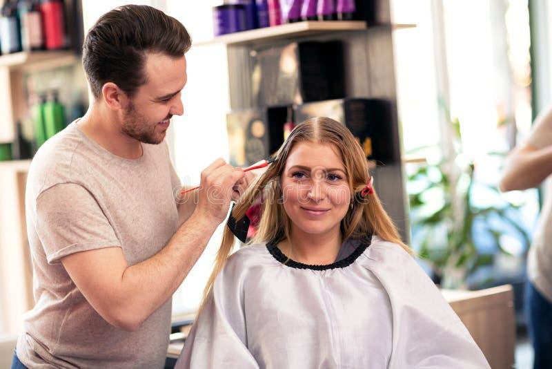 Kapper die kleurencliënt toepassen bij salon, die haarverf doen royalty-vrije stock foto
