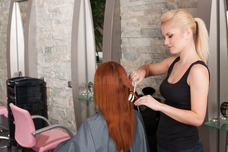 Kapper die rood haar met haarijzers rechtmaken stock fotografie